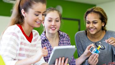 Schülerinnen gemeinsam am Tablet beim Bau eines Miniroboters