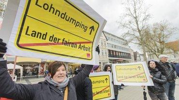 Frau mit Schild, das vor Lohndumping warnt